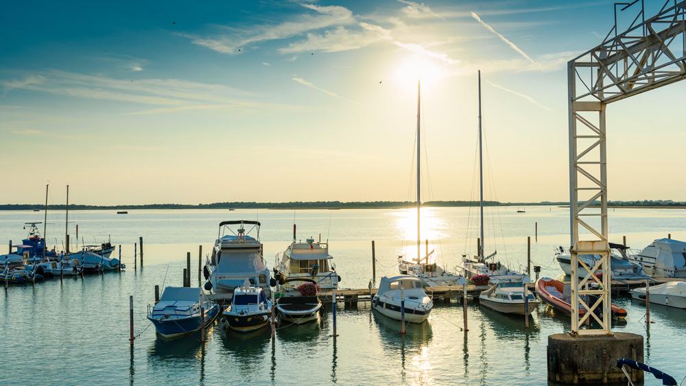 Sommerurlaub in Bibione. Urlaub in Bibione mit Kind. Italienurlaub Tipp. Sonnenuntergang am Hafen